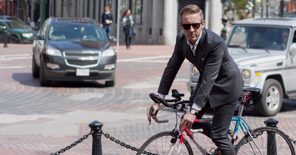Man in suit on a road bike