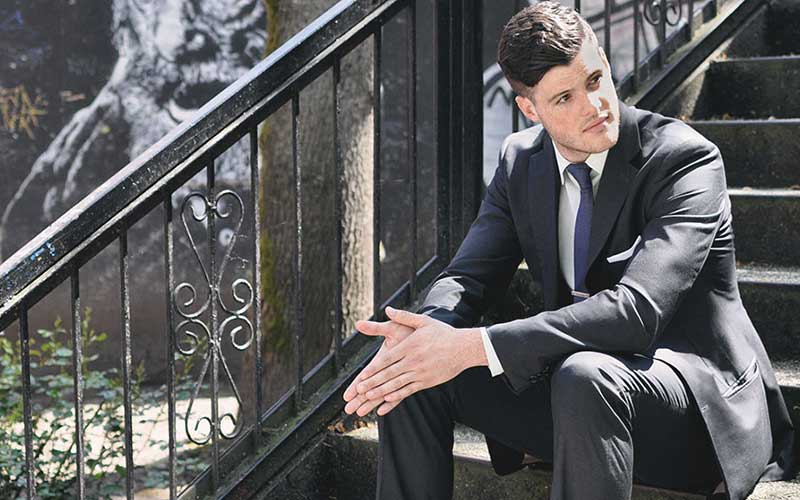 Chris Baird in a charcoal suit sitting on steps.