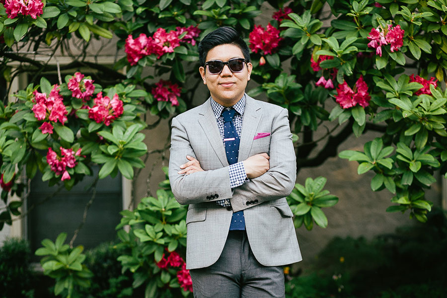 Viranlly Liemena wearing a gray suit and sunglasses in front of flowers.