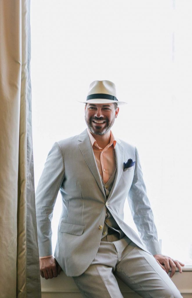 Tyson Villeneuve in a light coloured suit and hat.