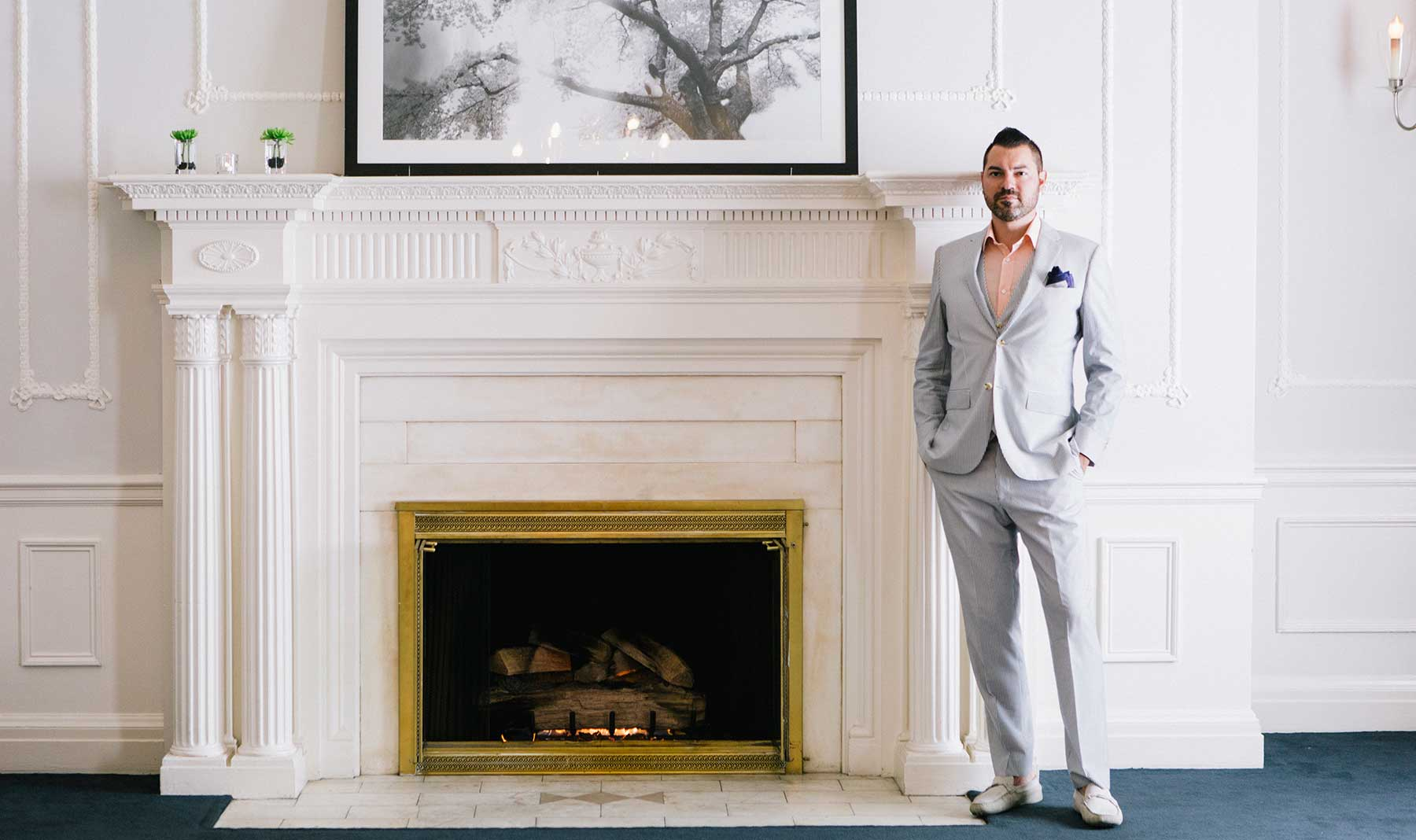 Tyson Villeneuve in a light coloured suit in front of a fireplace.
