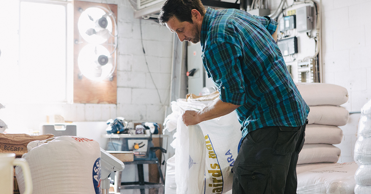 Don Farion pouring a bag of malt to make craft beer.