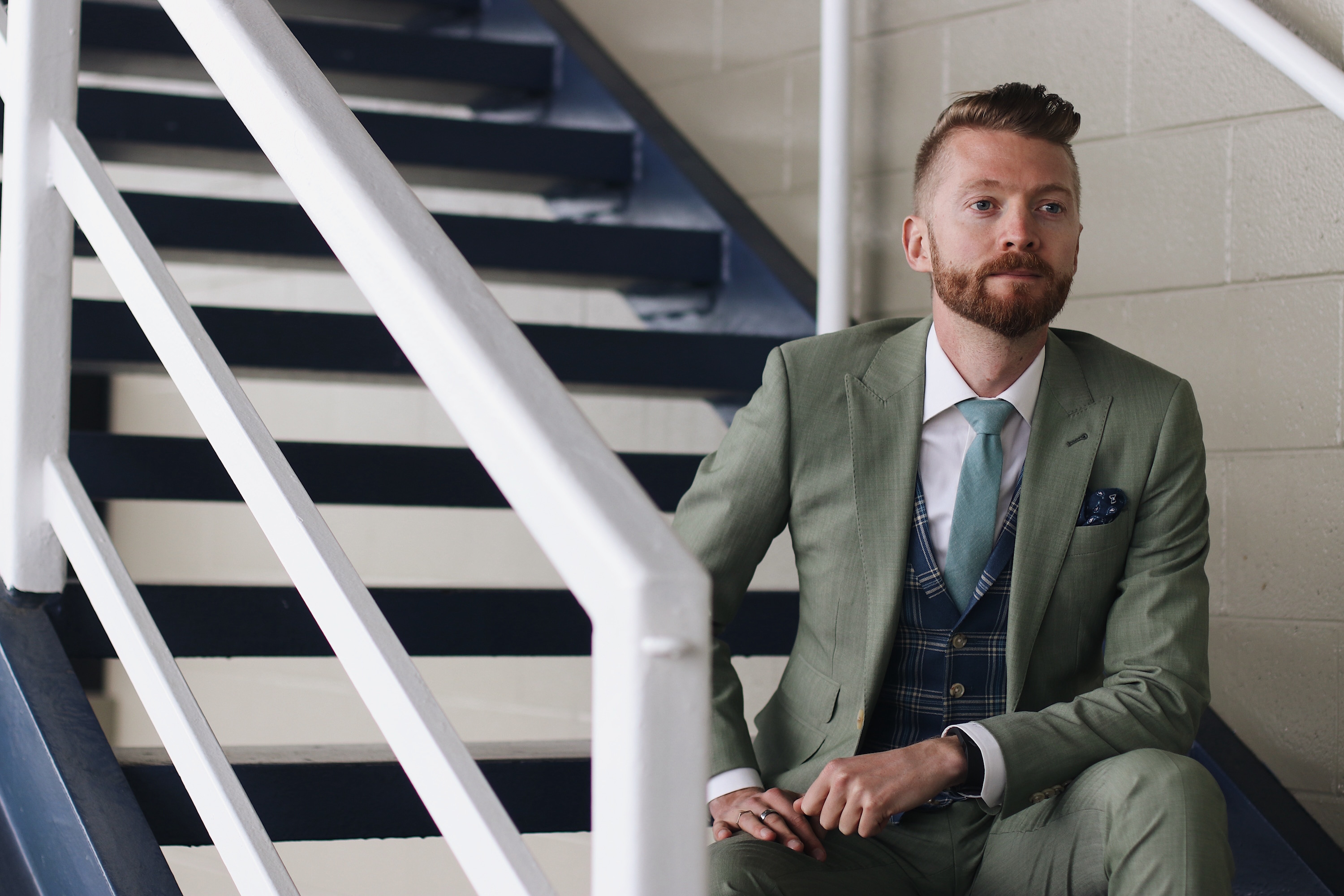 Jordan raises the style stakes in INDOCHINO's Sage Green Wool Stretch Suit and the Blue and Ivory Plaid Blazer.
